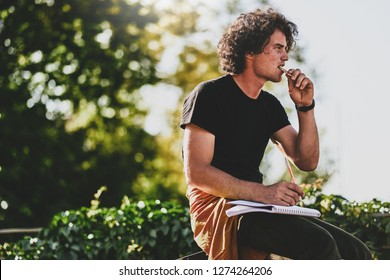Side view portrait of good-looking man student with curly hair, wearing black t-shirt, eating snack and preparing for exam. Freelancer businessman planning the day sitting on the city street