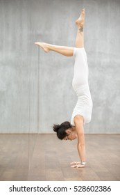 Side view portrait of gorgeous young woman with beautiful tattoo on her leg working out in fitness club, doing yoga or pilates exercise. Handstand, Adho Mukha Vrksasana, Downward facing Tree Pose