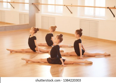 Side view portrait of group of little girls stretching legs during warm up at ballet practice, lit by sunlight