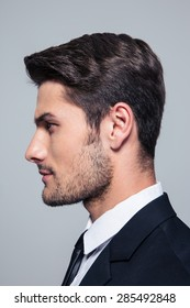 Side view portrait of a handsome businessman over gray background
