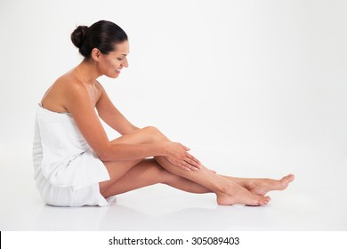 Side view portrait of a happy beautiful woman sitting on the floor isolated on a white background