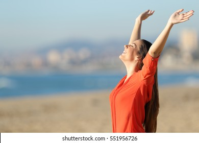 Side view portrait of a happy beautiful woman breathing and raising arms on the beach in a sunny day
