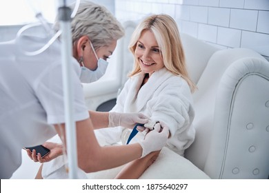 Side view portrait of happy cheerful talking with professional doctor while receiving IV infusion in beauty clinic