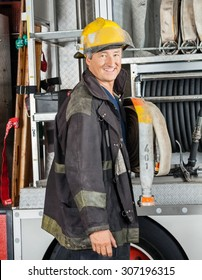 Side view portrait of happy male firefighter standing by truck at fire station