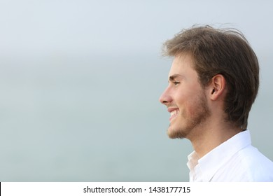 Side view portrait of a happy man looking away on the beach