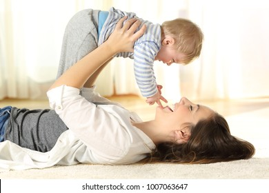 Side view portrait of a happy mother lying on the floor raising her baby son at home