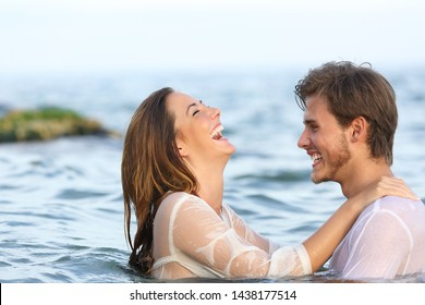 Side view portrait of a happy spontaneous couple joking in the water on the beach