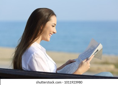 Side view portrait of a happy woman reading a newspaper sitting on a bench on the beach