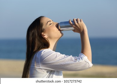 Side view portrait of a happy woman refreshing drinking soda sitting on a bench on the beach