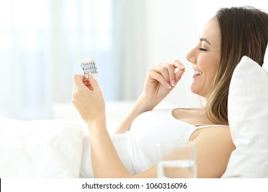 Side view portrait of a happy woman taking contraceptive pill in the bed at home