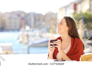 Side view portrait of a happy woman breathing fresh air in a coffee shop on vacation on the beach