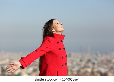 Side view portrait of a happy woman breathing deep in the city