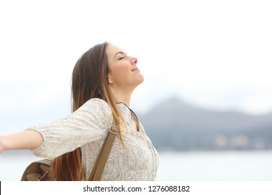 Side view portrait of a happy woman breathing fresh air on the beach or lake