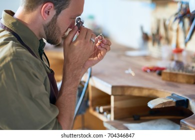 Side view portrait of jeweler inspecting diamond ring through magnifying glass in workshop