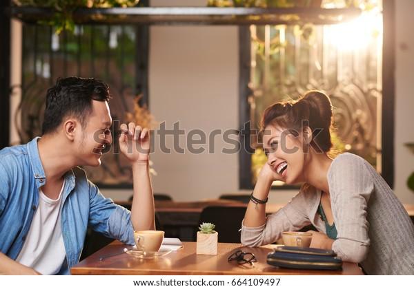 Retrato de vista lateral de una pareja asiática riéndose disfrutando de una cita en un café