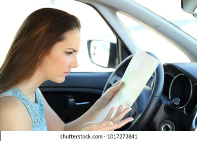 Side view portrait of a lost driver sitting inside her car trying to find direction in a guide