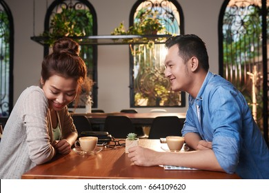Side view portrait of loving Asian couple meeting in cafe for date, chatting and flirting affectionately