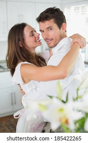 Side view portrait of a loving young couple embracing at home