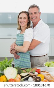 Side view portrait of a man embracing woman in the kitchen at home