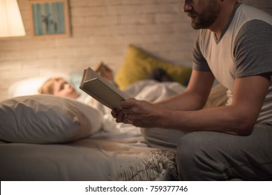 Side view portrait of man reading bedtime story to little son sitting on edge of bed in dim light with blurred shape of child sleeping in background.
