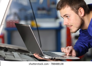 Side view portrait of a mar car mechanic checking electronic components with a laptop in a workshop