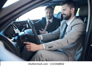 Side view portrait of mature bearded businessman sitting inside brand new car in dealership showroom taking it for test drive