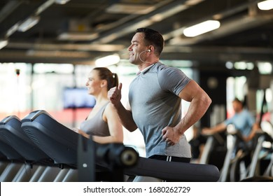 Side view portrait of mature muscular man running on treadmill while enjoying cardio workout with music in modern gym, copy space