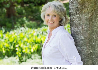 Side view portrait of a mature woman leaning against tree trunk in the park