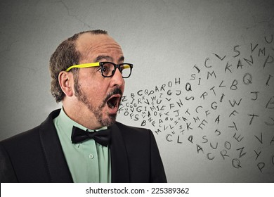 Side view portrait middle aged business man talking with alphabet letters coming out of open mouth isolated grey wall background. Human face expression emotion perception. Communication concept