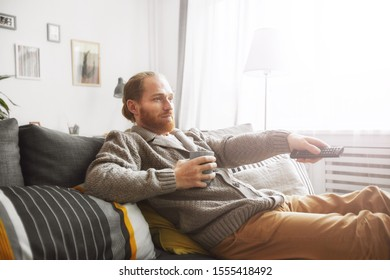 Side view portrait of middle-aged bearded man watching TV at home and switching channels via remote control while relaxing on comfortable couch