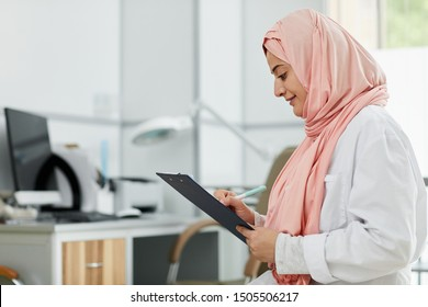 Side view portrait of Middle-Eastern woman wearing hijab working as nurse in medical clinic and writing on clipboard, copy space