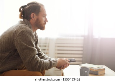 Side view portrait of modern bearded man watching TV at home and holding remote control, copy space