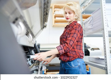 Side view portrait of modern blonde woman working with plotters in printing shop of publishing company