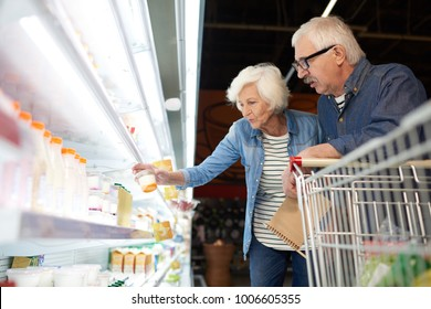 Side view portrait of modern senior couple choosing milk products standing by dairy isle in supermarket while grocery shopping, copy space