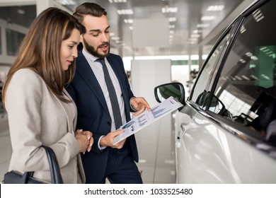 Side view portrait of modern young woman listening to car dealer while choosing luxury car in showroom, copy space