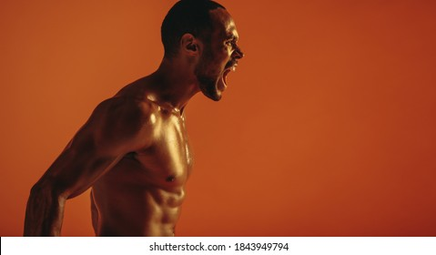 Side view portrait of muscular man shouting aggressively. Cropped shot of bare chested african american man shouting.