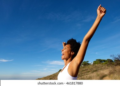 Side view portrait of overjoyed fit woman standing outdoors with her hands raised