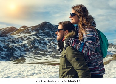 Side view portrait of a pensive couple or marriage hugging and looking to natural snowy landscape wearing gloves, coat and glasses with mountain peak in the background enjoying sun light warmth