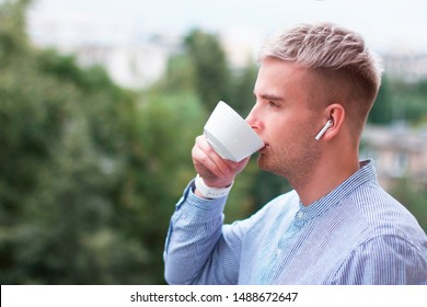 Side view portrait of pensive meditative blonde guy in shirt, earbuds with cup of coffee or tea. Young man with dyed gray hair listening to music in wireless earphones drinking drink outdoor in a park