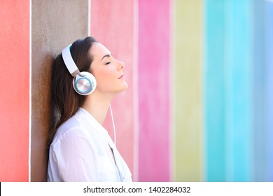 Side view portrait of a relaxed girl listening to music in a colorful street
