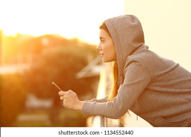 Side view portrait of a relaxed teen holding a smart phone looking away at sunset