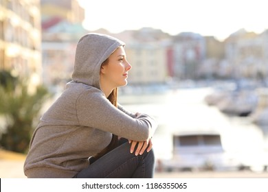 Side view portrait of a relaxed teen looking away in a coast town street