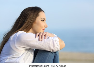 Side view portrait of a relaxed woman thinking and looking away on the beach