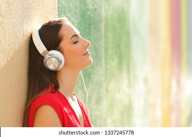 Side view portrait of a relaxed woman listening to the music in a colorful street