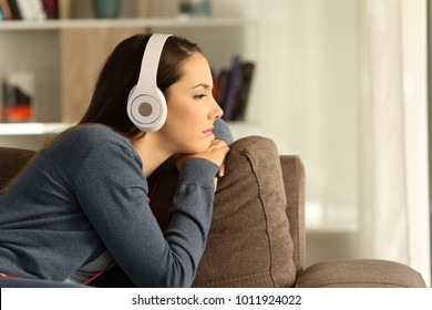 Side view portrait of a sad pensive woman listening to music sitting on a couch in the living room at home