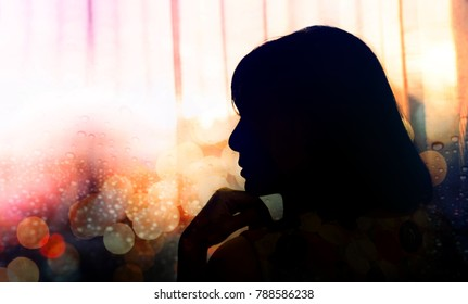 Side View Portrait of a Sadness Woman, Hand on Chin, Silhouette and Double Exposure style, blurred City light bokeh and Rain drop on glass window as background