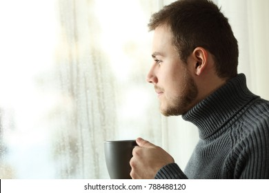 Side view portrait of a satisfied man looking through a window holding a coffee cup at home in a rainy day