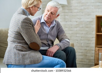 Side view portrait of senior man talking to female psychiatrist during therapy session, copy space