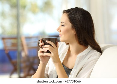 Side view portrait of a serious pensive woman relaxing holding a coffee mug looking away sitting on a sofa in the living room in a house interior