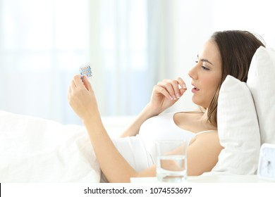 Side view portrait of a serious woman taking a contraceptive pill on the bed at home